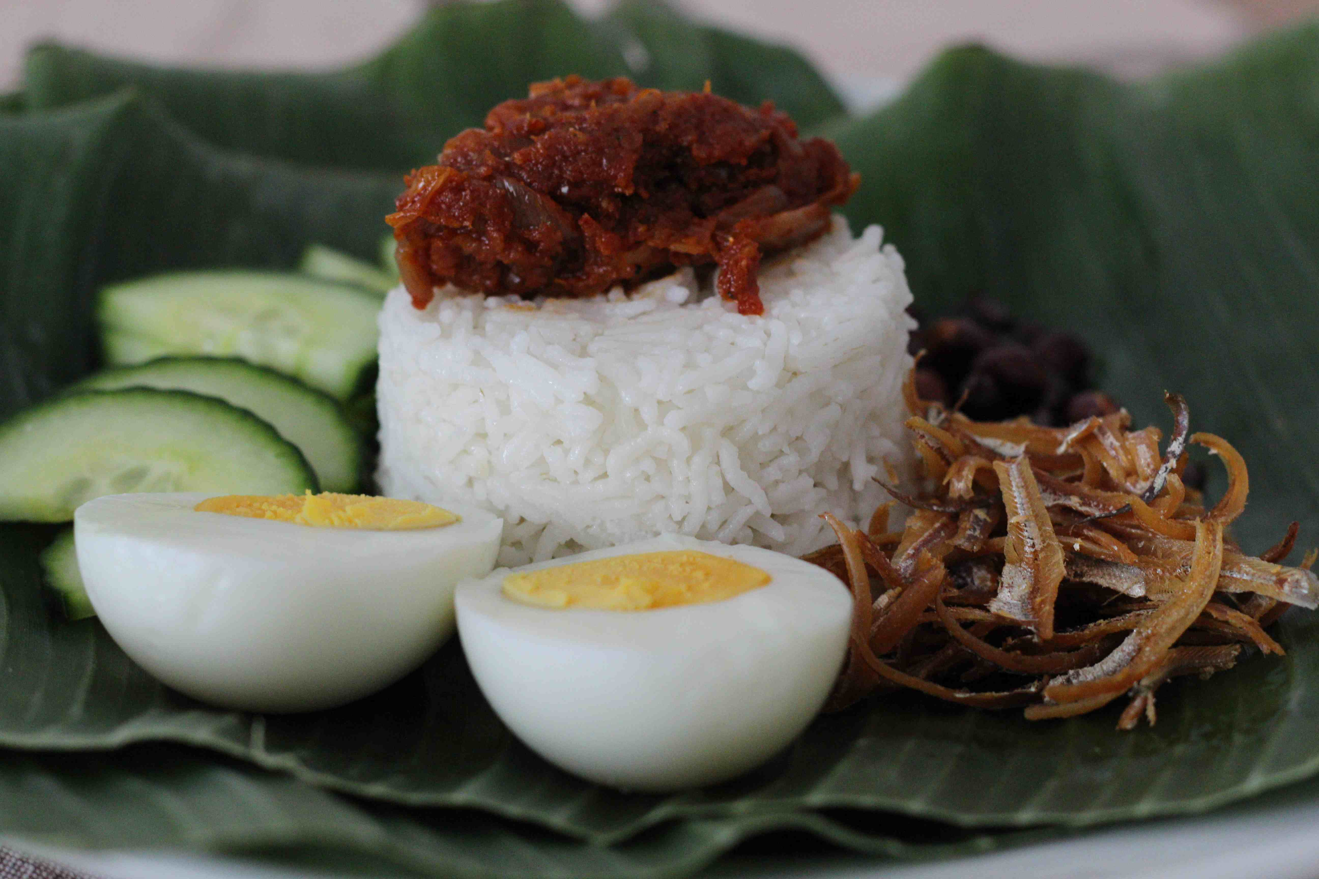 malaysia famous food nasi lemak Known as one of the national dishes of malaysia, nasi lemak is a comfort food and a dish to truly look forward to there are a number of variations to the dish: the traditional triangle of rice wrapped in a banana leaf (kind of as a snack) and a meal version served on a plate.
